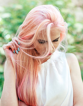 Benefits of Not Washing Hair Daily - Girl Holding Pink Hair & Looking Down